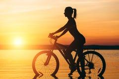 一个运动的女孩的剪影在水中坐一辆自行车在日落在一个温暖的夏日的衣服的 球概念健身pilates放松 天空bac 库存图片
