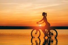 一个运动的女孩的剪影在水中坐一辆自行车在日落在一个温暖的夏日的衣服的 球概念健身pilates放松 天空bac 免版税库存图片