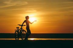 一个运动的女孩的剪影站立在一辆自行车附近的衣服的在水中和指向她的手距离在温暖的日落 库存照片