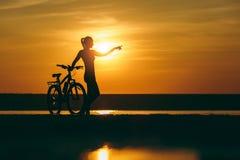 一个运动的女孩的剪影站立在一辆自行车附近的衣服的在水中和指向她的手距离在温暖的日落 库存图片