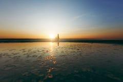一个运动的女孩的剪影站立在一辆自行车附近的衣服的在水中在日落在一个温暖的夏日 球概念健身pilates放松 天空ba 库存照片