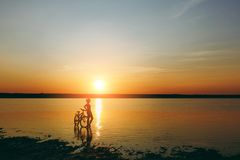 一个运动的女孩的剪影站立在一辆自行车附近的衣服的在水中在日落在一个温暖的夏日 球概念健身pilates放松 天空ba 图库摄影