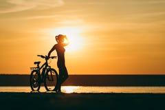 一个运动的女孩的剪影站立在一辆自行车附近的衣服的在水中在日落在一个温暖的夏日 球概念健身pilates放松 天空ba 库存图片