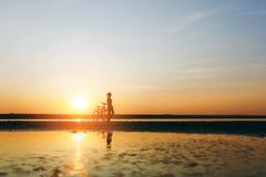 一个运动的女孩的剪影站立在一辆自行车附近的衣服的在水中在日落在一个温暖的夏日 球概念健身pilates放松 天空ba 免版税图库摄影