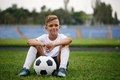 一个运动的男孩的照片有球的坐在体育场背景的一个绿色领域 活动,爱好概念 库存图片