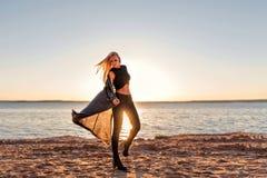 一个运动的身体的女孩跨步入舞蹈并且沿沙滩走在太阳的黎明在振翼黑暗的衣裳的  库存图片