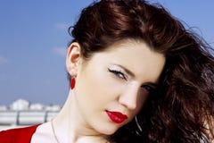 一个迷人的俏丽的女孩的画象有长的红色头发的 摆在夏天自然的背景的一名俏丽的妇女 免版税库存图片