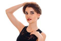 一个迷人的女孩的画象有红色唇膏的在举手到头发的嘴唇 免版税库存图片