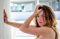 一个迷人的性感的女孩在一个热,晴朗的夏日支持在泳装的墙壁, 免版税库存图片