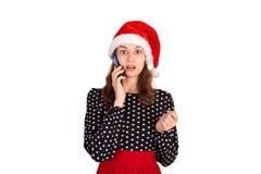 一个迷茫的逗人喜爱的女孩的画象礼服谈话的在手机 情感女孩在圣诞老人在白色后面隔绝的圣诞节帽子 免版税库存图片