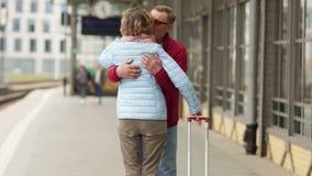 一个退休的人遇见火车平台的一名妇女 结合容忍和亲吻 股票录像