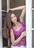 一个透明桃红色迷人的样式衣裳的美丽的长发妇女来自豪宅的老门 库存照片