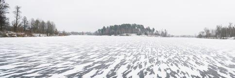 一个透明的结冰的湖在冬天,洒与雪 免版税图库摄影