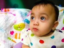 一个逗人喜爱和传神亚裔女婴的坦率的画象 生活方式和童年概念 免版税库存照片