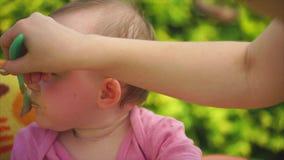 一个逗人喜爱和滑稽的孩子的画象,哺养与匙子的粥 影视素材