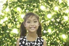 一个逗人喜爱的亚裔女孩享用与圣诞灯 库存照片