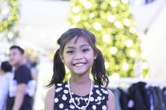 一个逗人喜爱的亚裔女孩享用与圣诞灯 免版税库存图片