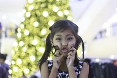 一个逗人喜爱的亚裔女孩享用与圣诞灯 库存图片