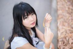 一个逗人喜爱的亚裔泰国女孩拿着一片干燥叶子并且做眼睛cont 免版税库存照片