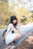 一个逗人喜爱的亚裔泰国女孩是坐和举行干燥叶子和mak 免版税库存照片