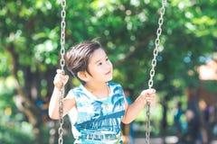 一个逗人喜爱的亚裔男孩愉快地演奏摇摆 免版税库存图片