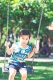 一个逗人喜爱的亚裔男孩愉快地演奏摇摆 库存照片