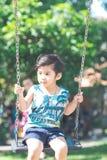 一个逗人喜爱的亚裔男孩愉快地演奏摇摆 库存图片