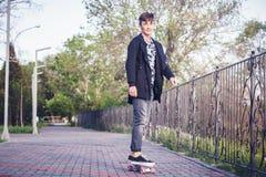 一个逗人喜爱的亚裔青少年的男孩的画象踩滑板15-16的岁 免版税图库摄影