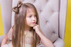 一个逗人喜爱的十几岁的女孩的画象黄色背景的在椅子 免版税图库摄影