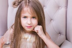 一个逗人喜爱的十几岁的女孩的画象黄色背景的在椅子 免版税库存图片