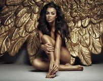 一个逗人喜爱的天使的画象与金子的飞过 库存图片