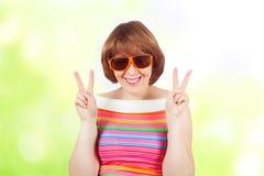一个逗人喜爱的女孩佩带的太阳镜和一件明亮的T恤杉 库存照片