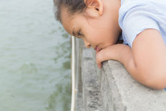 一个逗人喜爱的女孩凝视到海 免版税库存照片