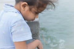 一个逗人喜爱的女孩凝视到海 库存图片