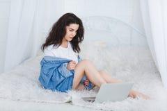 一个逗人喜爱的女孩坐床并且看一台开放膝上型计算机 免版税库存照片