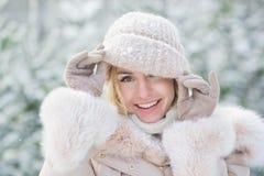 一个逗人喜爱的女孩的画象在握手一个被编织的帽子在一个冬天 库存照片