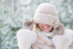 一个逗人喜爱的女孩的画象在穿上了一个被编织的帽子眼睛在一个冬天 库存照片
