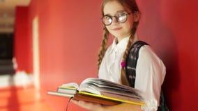 一个逗人喜爱的女孩的画象戴眼镜的 女小学生在她的手上拿着书,在她的后面后书包,回到 股票视频