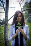 一个逗人喜爱的女孩的画象在有叶子的森林里 库存照片
