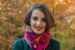 一个逗人喜爱的女孩的画象微笑的围巾和红色嘴唇的 库存照片
