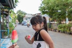 一个逗人喜爱的女孩的画象有冰淇凌的户外 免版税库存图片