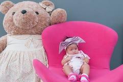 一个逗人喜爱的女婴的射击有紫色头饰带的和大玩具熊,当睡觉和使用在桃红色椅子/聚焦在婴儿时 库存图片