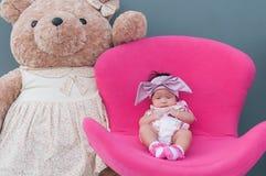 一个逗人喜爱的女婴的射击有紫色头饰带的和大玩具熊,当睡觉和使用在桃红色椅子/聚焦在婴儿时 免版税库存图片