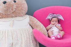 一个逗人喜爱的女婴的射击有紫色头饰带的和大玩具熊,当睡觉和使用在桃红色椅子/聚焦在婴儿时 库存照片