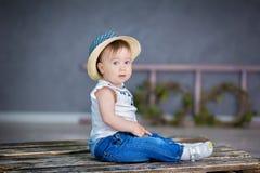 一个逗人喜爱的女婴的画象轻的背景的与花花圈在她的头的坐沙发篮子 库存图片
