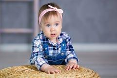 一个逗人喜爱的女婴的画象轻的背景的与花花圈在她的头的坐沙发篮子 免版税库存照片