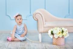 一个逗人喜爱的女婴的画象轻的背景的与花花圈在她的头的坐沙发篮子 免版税库存图片