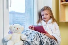 一个逗人喜爱的婴孩在屋子里坐在窗口在冬天并且读书 库存图片