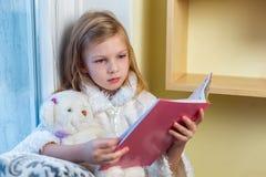一个逗人喜爱的婴孩在屋子里坐在窗口在冬天并且读书 免版税库存照片