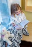 一个逗人喜爱的婴孩在屋子里坐在窗口在冬天并且读书 图库摄影